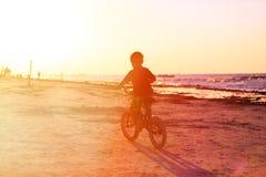 小男孩在日落的骑马自行车 库存图片