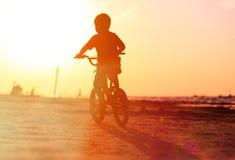 小男孩在日落的骑马自行车 免版税库存图片