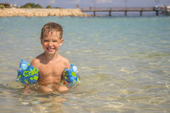 小男孩在有可膨胀的过袖子的海 库存图片