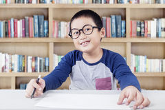 小男孩在有标志和纸的图书馆里 免版税库存图片