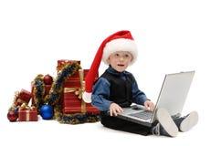 小男孩在有膝上型计算机和圣诞节礼物的圣诞老人盖帽 免版税图库摄影