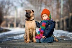 小男孩在有他的狗朋友的公园 库存图片