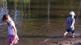 小男孩在池塘边缘跑在女孩附近 股票视频