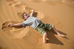 小男孩在沙漠做沙子天使 免版税库存照片