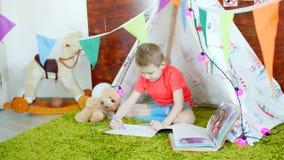 小男孩在游戏室的图画册页写妈妈 免版税库存照片