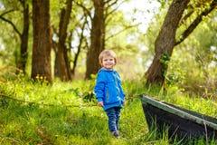 小男孩在湖的一条木小船附近站立 免版税库存图片
