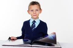 小男孩在白色读一本书,被隔绝 免版税库存照片