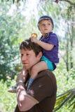 给小男孩在肩膀的愉快的年轻父亲乘驾 库存照片