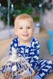 小男孩在蓝色睡衣的圣诞树附近坐有熊的 免版税库存照片