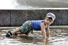 小男孩在水中的做一个俯卧撑 免版税库存图片