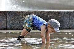 小男孩在水中的做一个俯卧撑 图库摄影
