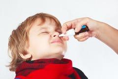 小男孩在鼻子使用了医疗鼻孔喷射 库存图片