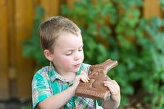 小男孩在他的手上的看巧克力兔宝宝 库存图片