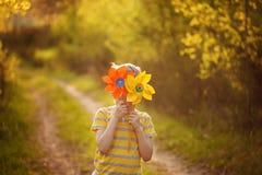 小男孩在绿色森林背景的黄色和橙色轮转焰火后掩藏在晴天 库存照片