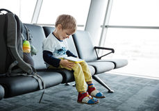 小男孩在满足使用机场离开的大厅里坐他的片剂或手机 免版税库存图片