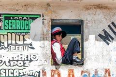 小男孩坐一老houuse的窗口在库斯科,秘鲁 库存照片