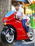 小男孩坐一辆玩具摩托车在游乐园 免版税库存图片