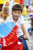 小男孩坐一辆玩具摩托车在游乐园 图库摄影