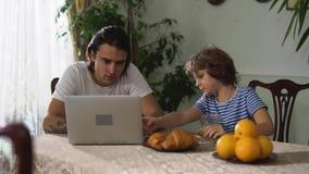 小男孩坐吃与热奶咖啡和老年人兄弟观看的手提电脑的厨房用桌新月形面包 股票视频