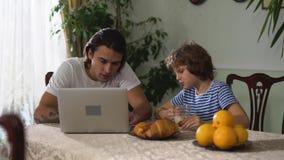 小男孩坐吃与热奶咖啡和老年人兄弟观看的手提电脑的厨房用桌新月形面包 股票录像
