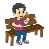 小男孩坐吃冰淇凌动画片的长凳 免版税库存图片