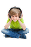 小男孩坐听到音乐的白色地板 库存照片
