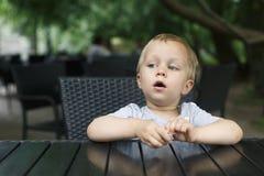 小男孩坐在咖啡馆的一张桌上 库存照片