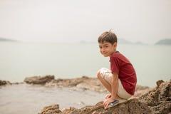 小男孩坐在愉快海滩面孔的看起来的岩石 库存图片