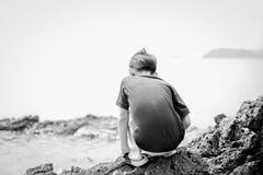 小男孩坐在愉快海滩面孔的看起来的岩石 图库摄影