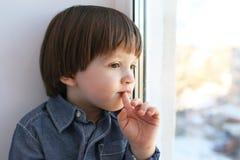 小男孩坐基石并且看在窗口外面在冬天 免版税图库摄影