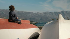 小男孩坐小船,看起来远的近的海户外 股票视频