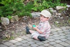 小男孩坐拿着一个绿色复活节彩蛋 图库摄影
