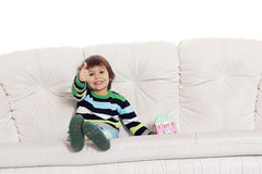 小男孩坐有显示手好si的玩具房子的沙发 免版税图库摄影