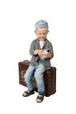 小男孩坐有闹钟的葡萄酒手提箱在手上 免版税库存图片