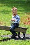 小男孩坐有绿色草坪的跷跷板在背景中 图库摄影