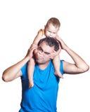 小男孩坐爸爸的肩膀,他们打趣味游戏 免版税库存照片