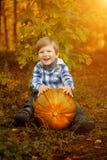 小男孩坐用南瓜和微笑 儿童enjo 免版税库存照片