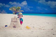 小男孩大厦在海滩的沙子城堡 图库摄影