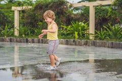 小男孩奔跑通过水坑 室外的夏天 免版税库存照片