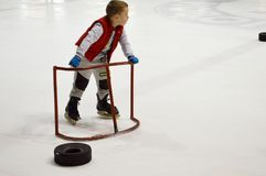 小男孩学会在冰球竞技场的特别支持的门, 2018年4月14日,白俄罗斯帮助下滑冰 库存照片