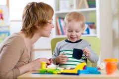 小男孩学会用五颜六色的戏剧面团在母亲帮助下 免版税图库摄影