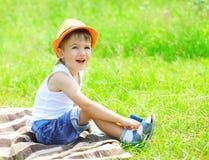 小男孩孩子画象帽子的坐草 图库摄影