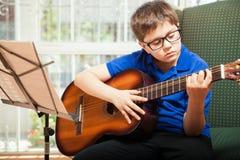小男孩实践的吉他 免版税库存图片