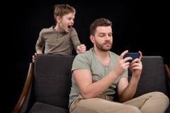 小男孩尖叫对使用智能手机的父亲 库存照片