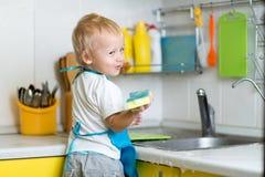 小男孩帮助的母亲洗涤的盘在厨房里 库存图片