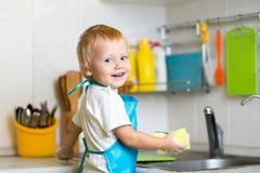 小男孩帮助的母亲洗涤的盘在厨房里 免版税库存照片