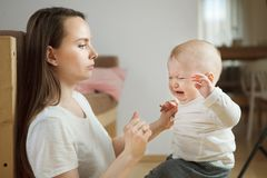 小男孩开始哭泣,看他的严肃的担心的母亲 免版税库存图片
