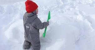 小男孩开掘与铁锹随风飘飞的雪 影视素材