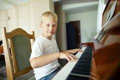 小男孩弹钢琴 免版税库存照片