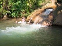 小男孩快乐地笑并且显示一个正号用他的在小起泡的瀑布背景的手  免版税图库摄影